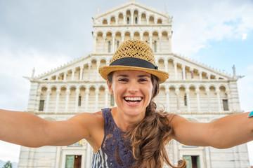Happy young woman making selfie in front of duomo di pisa, pisa