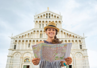 Happy young woman with map in front of duomo di pisa, pisa