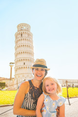 Portrait of happy mother and baby girl in front of tower of Pisa