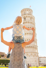Baby sitting on mothers shoulders and looking on tower of Pisa