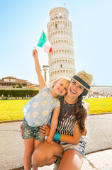 Portrait of happy mother and baby girl with italian flag in Pisa