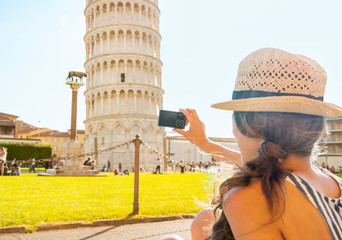 Young woman taking photo of leaning tower of pisa, tuscany