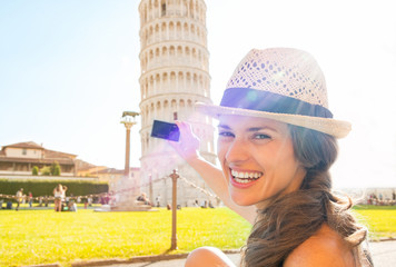 Happy young woman taking photo of leaning tower of pisa, tuscany