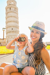 Mother and baby girl taking photo in front of tower of pisa