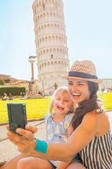 Happy mother and baby girl making selfie in Pisa