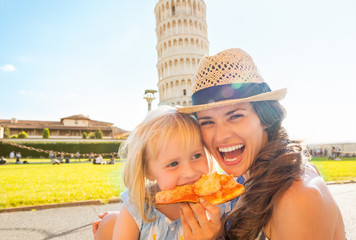Portrait of happy mother and baby girl eating pizza in Pisa