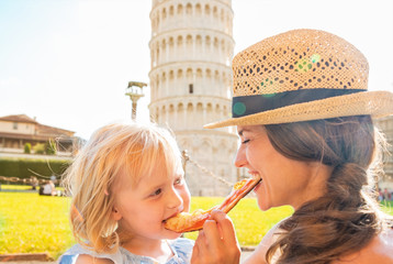 Happy mother and baby girl eating pizza in Pisa