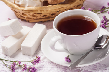 Cup of black tea with fruit candy