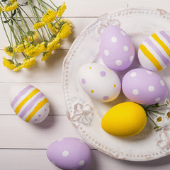 Colorful Easter eggs and flowers of the field in the plate. Top