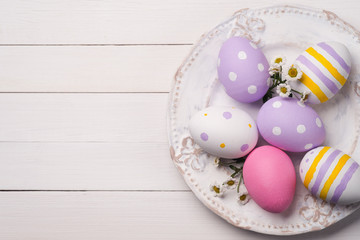 Colorful Easter eggs and flowers of the field in the plate. Spac