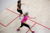 Two female squash players in fast action on a squash court