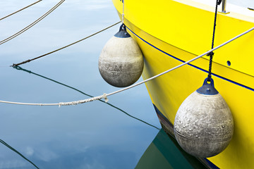 Detail of a yellow boat, buoys, ropes and sea water
