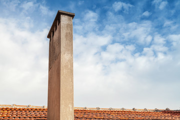 Chimney on red tile roof with cloudy sky background