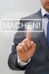 Mann drückt MACHEN-Knopf