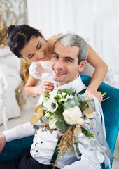 Cheerful married couple in white room