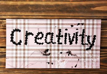 Word creativity written on paper on wooden background