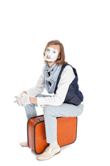 mime actor sitting on suitcase