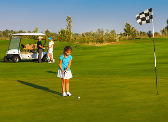Sportive family playing golf on a golf course