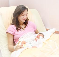 Newborn baby girl sleeping. Her mother looking at.