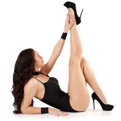 Brunette woman in swimsuit studio shot. Model posing on floor.