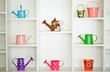 Shelf decoration with colorful gardening tools - watering cans