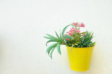 Yellow plant pot with flower hanging on wall