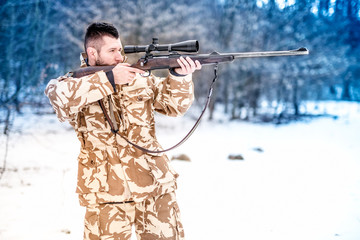 Military man holding a sniper rifle and aiming at enemy