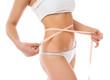 Slim woman measuring waist with tape measure - 78731384