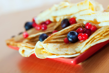 pancakes on plate with cranberries and blueberries