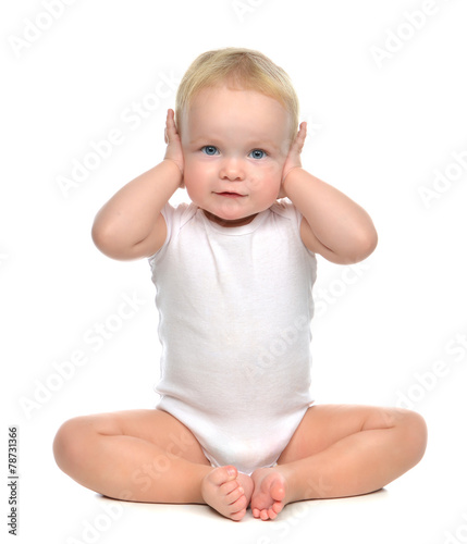 Leinwanddruck Bild infant child baby toddler sitting closed her hands over ears and