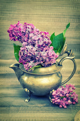 Lilac flowers in antique vase on wooden background. Vintage styl