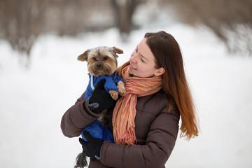girl keeps hugging dog in blue overalls on park