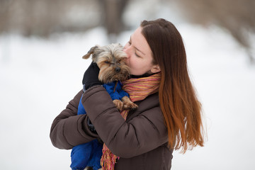 girl in  bright scarf keeps hugging dog  on hand