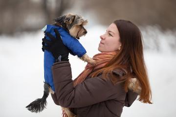 redhead girl in  bright scarf keeps  dog on hand