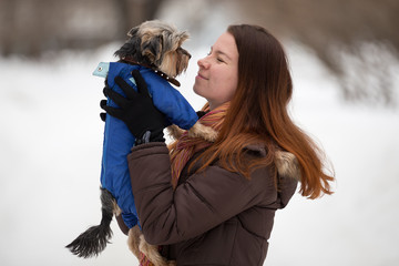 girl in a bright scarf keeps  dog in blue overalls on hand