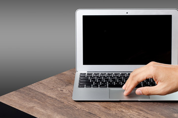 hand using a laptop on wood table, gray color background