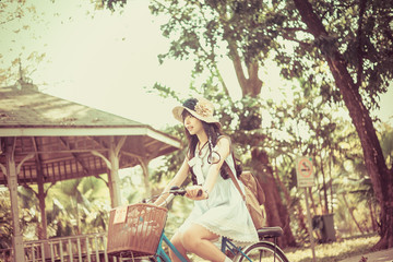 Cute Asian Thai girl in vintage clothings is riding a bicycle, i