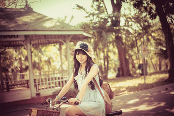 Cute Asian Thai girl is riding a bicycle in vintage color tone