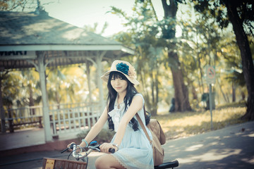 Cute Asian Thai girl in vintage clothing is riding a bicycle