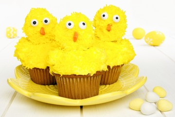 Spring chick cupcakes on yellow plate with Easter eggs