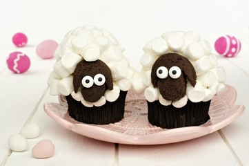 Cute spring sheep cupcakes on pink plate with Easter eggs