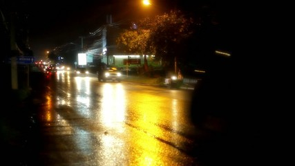 Cars and motorbikes driving on a wet road at night after rain