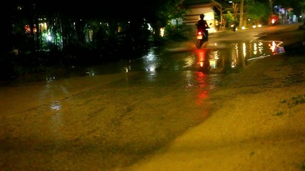 motorbikes drives through a puddle on the road at night after