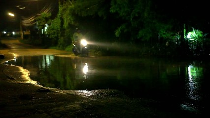 Motorbike  drives through a puddle on the road at night after