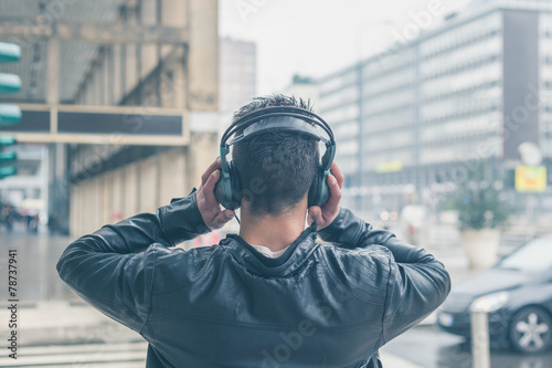 Back view of a young man with headphones posing in the city stre - 78737941