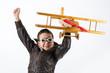 Jubelndes Kind mit Fliegerbrille und Holzflugzeug