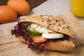 Sandwich with salmon and egg for breakfast, wooden background