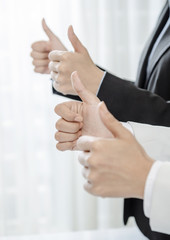 Row of human hands showing thumb up