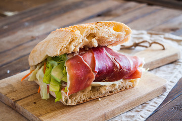 Sandwich with parma ham and salad on wooden cutting board