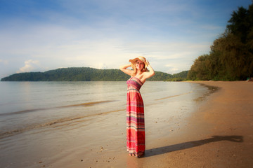 blonde barefoot girl in straw hat on beach against hill